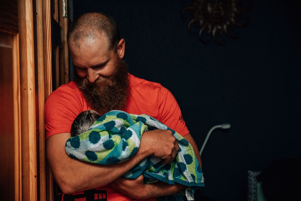 New dad smiles at his newborn baby after a home birth in Northwest Arkansas