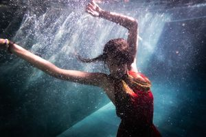 A woman in a red dress underwater