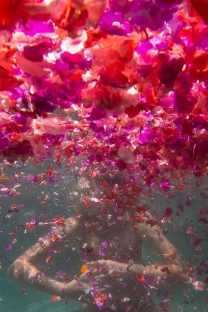 A woman embraces herself underwater surrounded by flowers