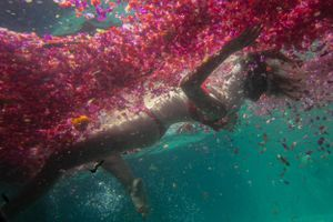 A woman falling through water and a sea of flowers