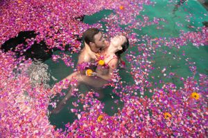 A couple embrace in a pool of flowers