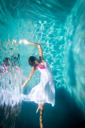 A woman in a white dress underwater poses like a ballerina