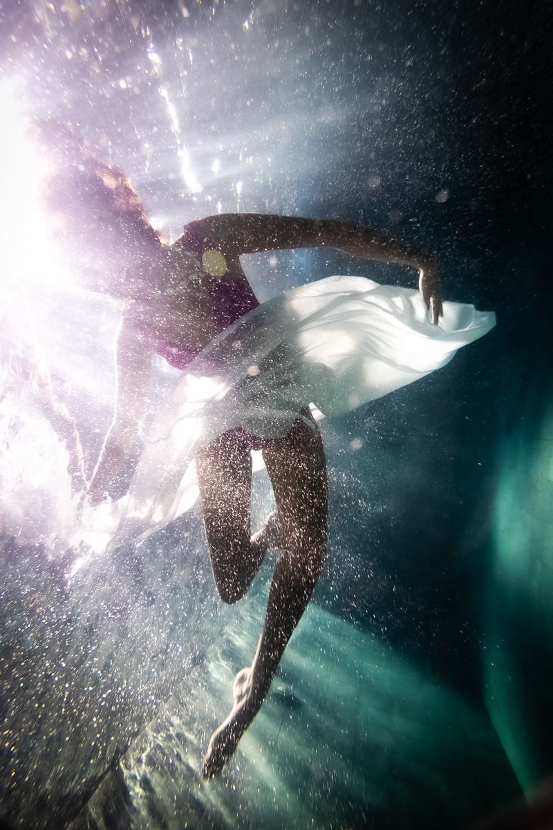 An underwater silhouette of a ballerina
