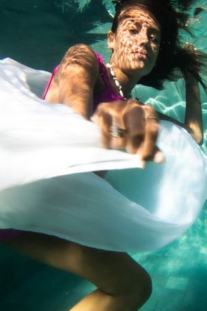 A woman underwater playing with her white skirt