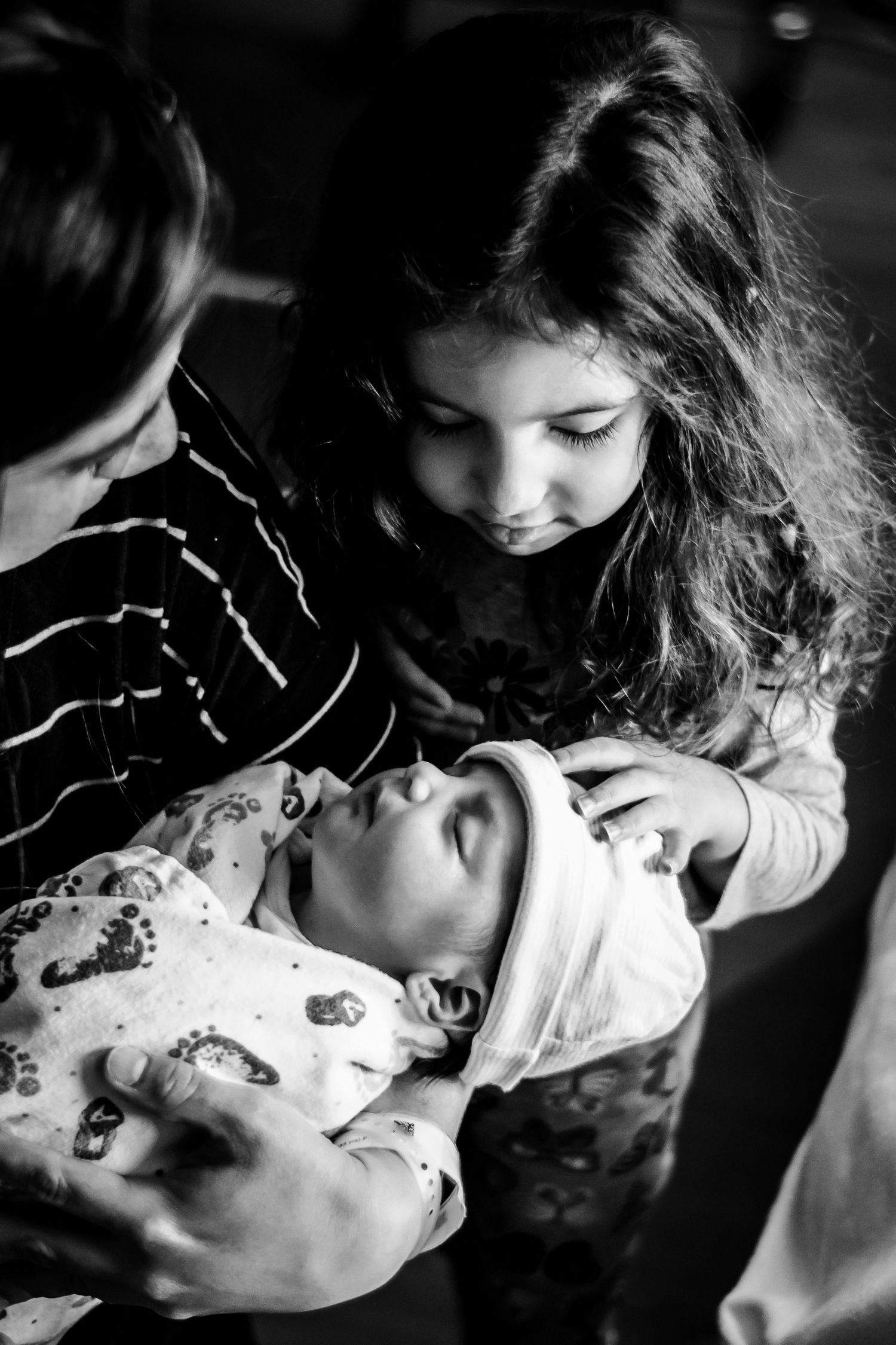 Big sister meeting her new baby sister during their Sibling visit session in Sioux City, IA.