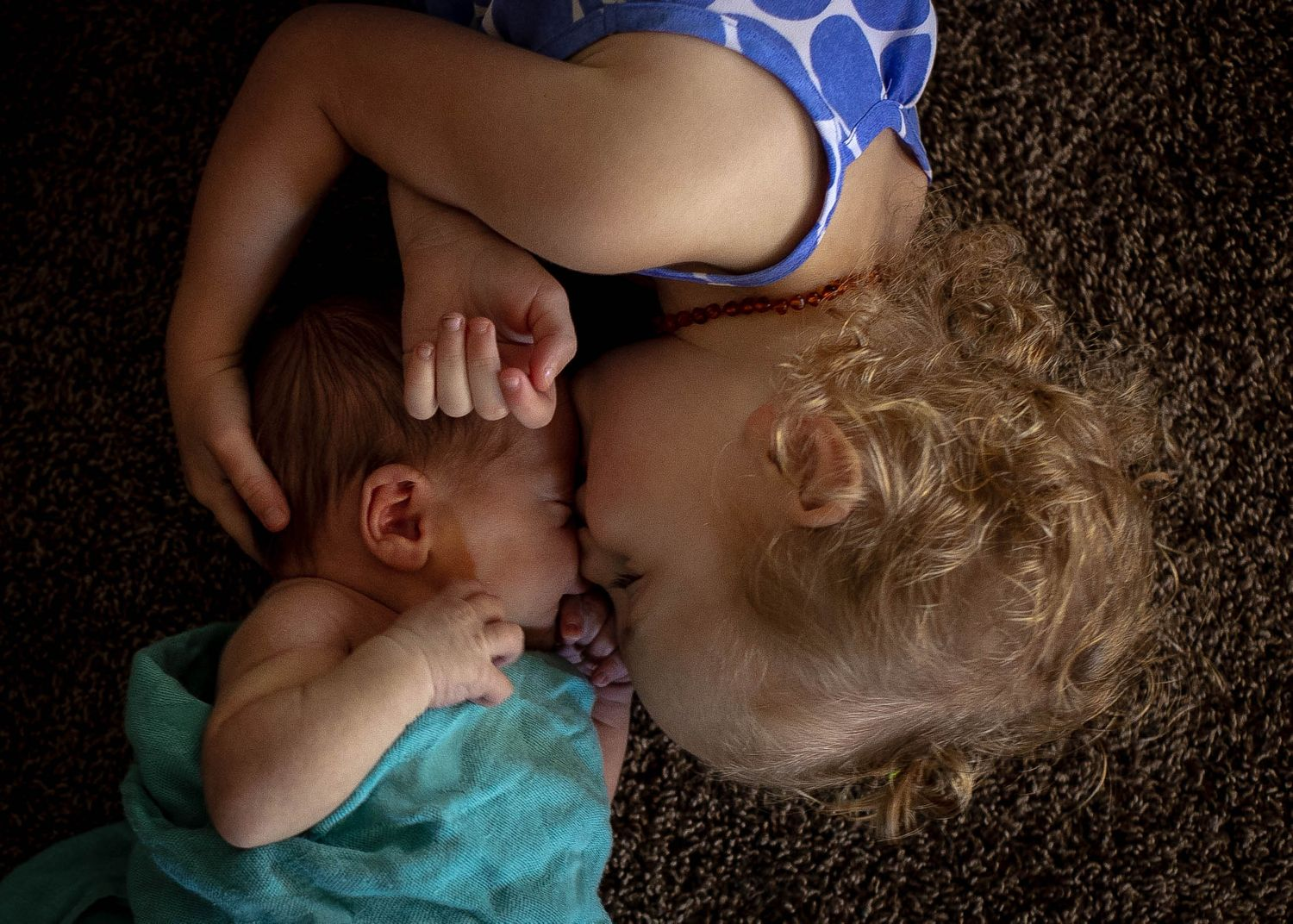 Big sister giving her new baby brother a kiss and snuggles during their in-home newborn session in Sioux City, IA.