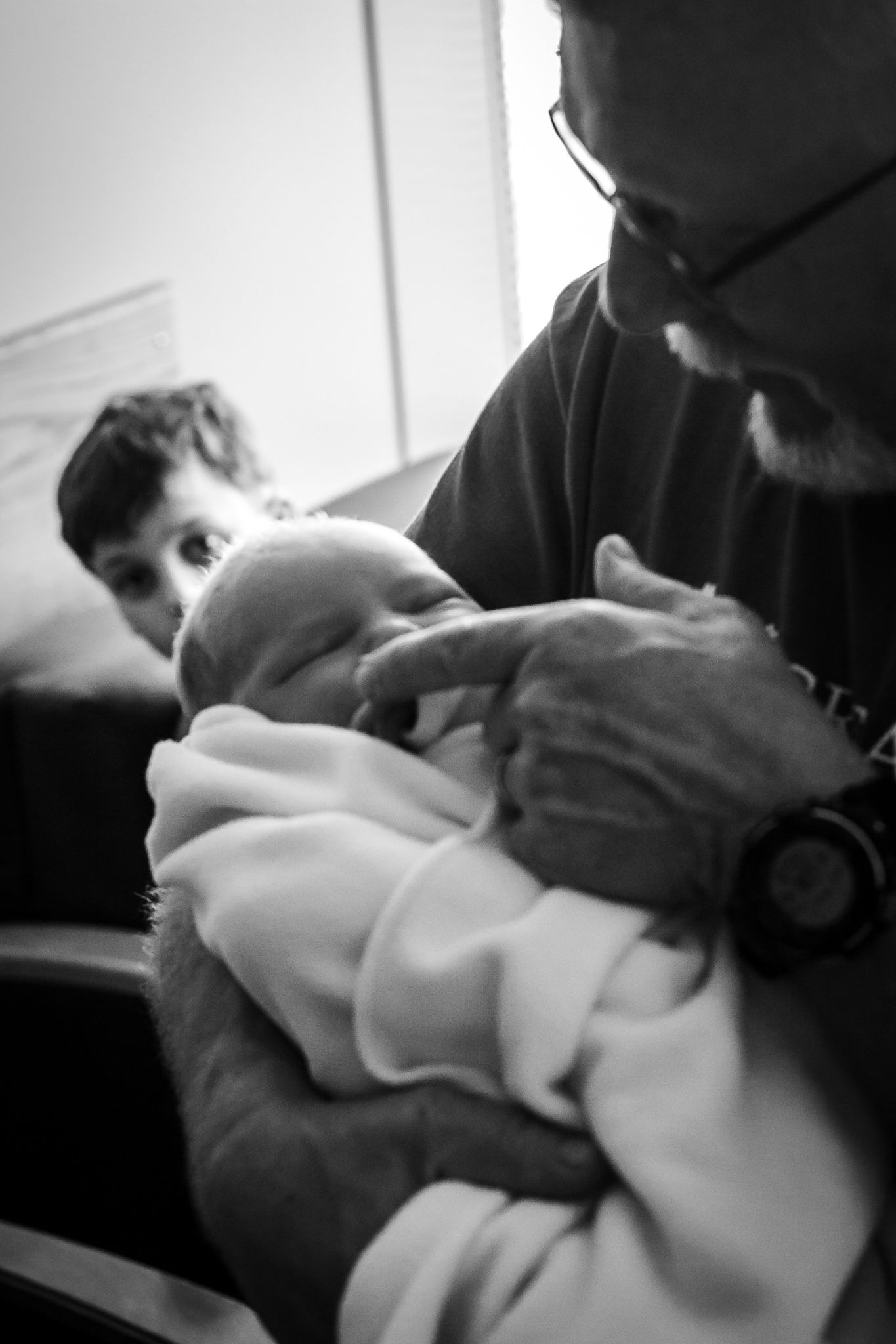Grandfather holding his newest granddaughter for the first time just after birth.