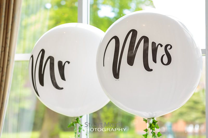 mr and mrs large white balloons floating above the top table at craxton wood
