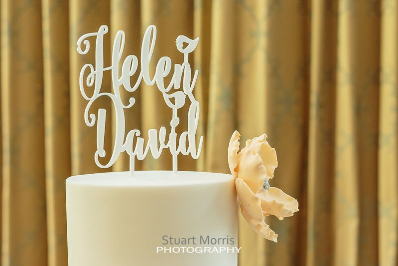 helen and david cake topper sits proudly atop their wedding cake