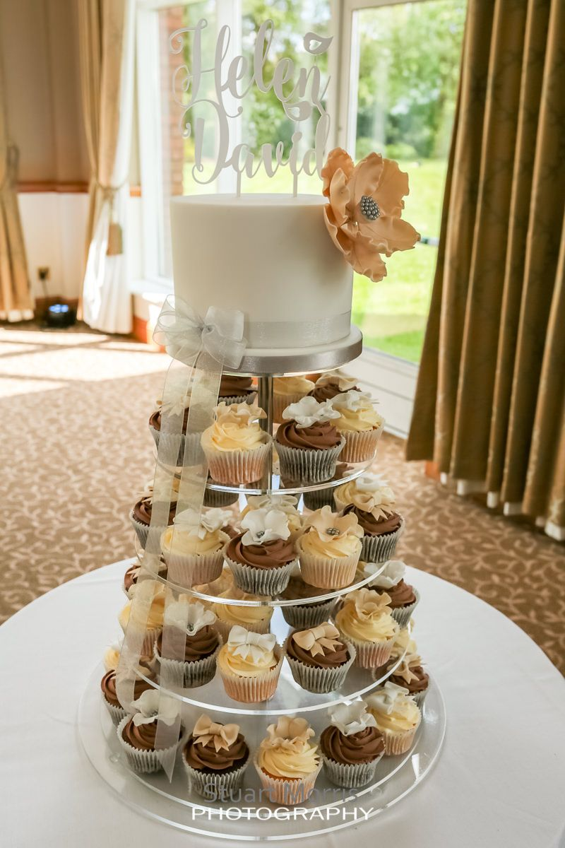 cup cakes sitting on a cake stand with a simple small wedding cake on the top
