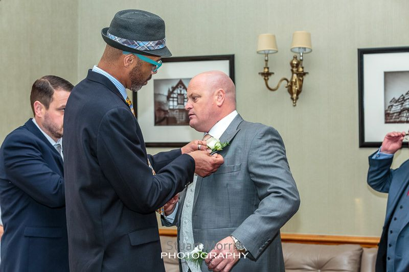 wedding guest wearing a trilby helps the groom attach his button hole to his lapel