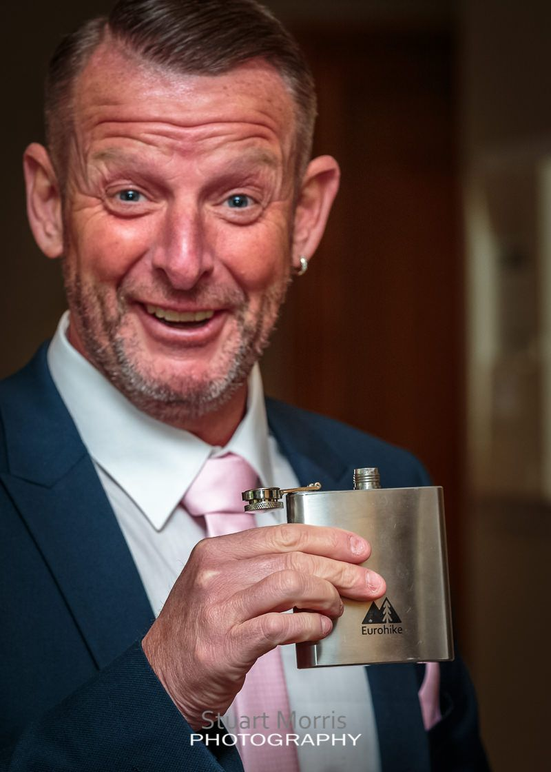 wedding guest showing off his hip flask before the ceremony
