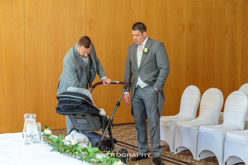 one of the groomsmen sees to his baby in the pram watched by another groomsman