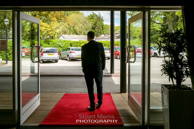 wedding guest waits in the craxton wood doorway on the red carpet for the bride to arrive