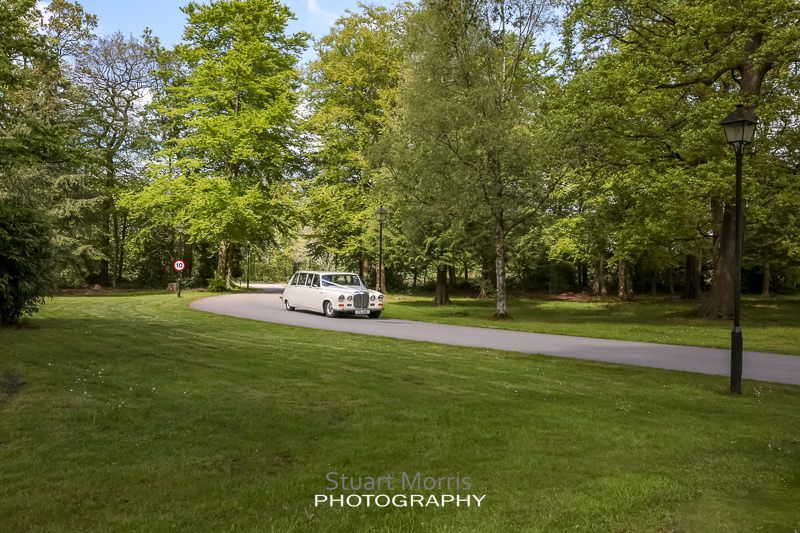 the wedding car makes its way up the craxton wood driveway with the bride