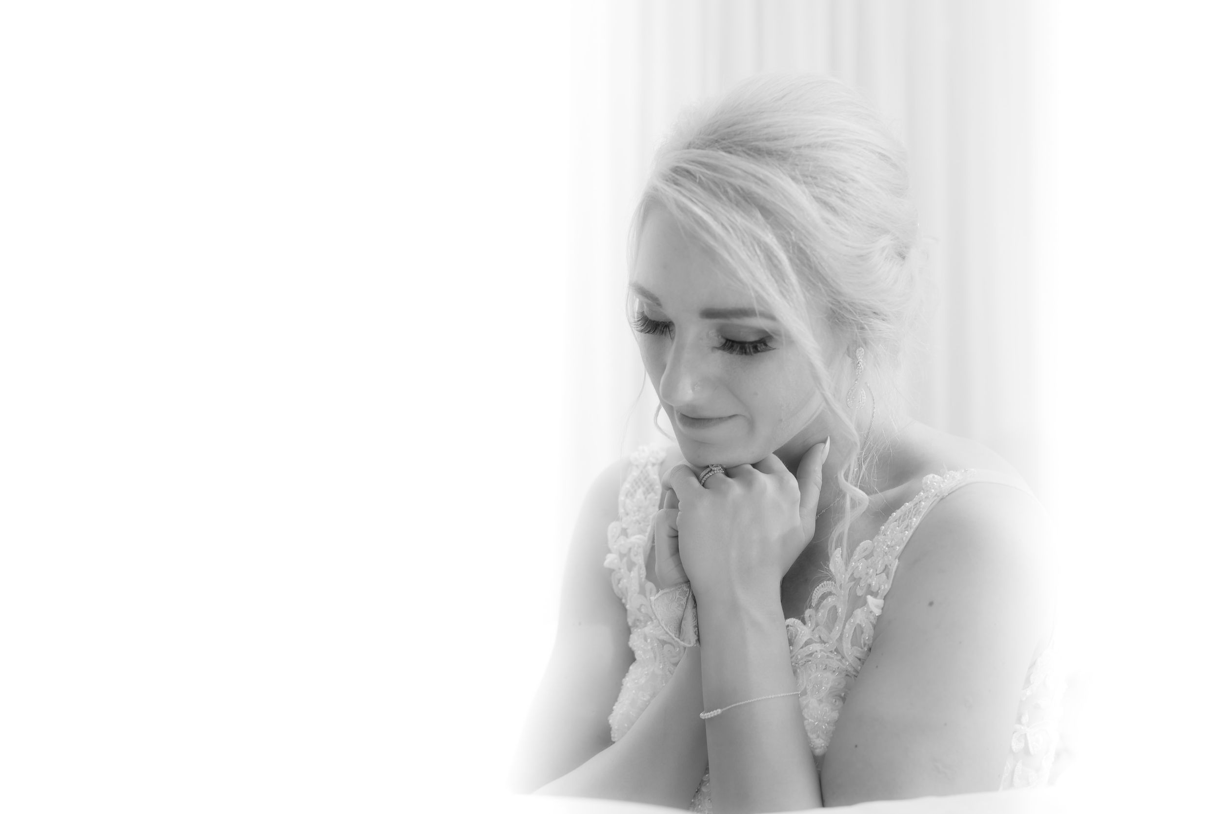Tender moment of reflection by bride during speeches, black and white photography