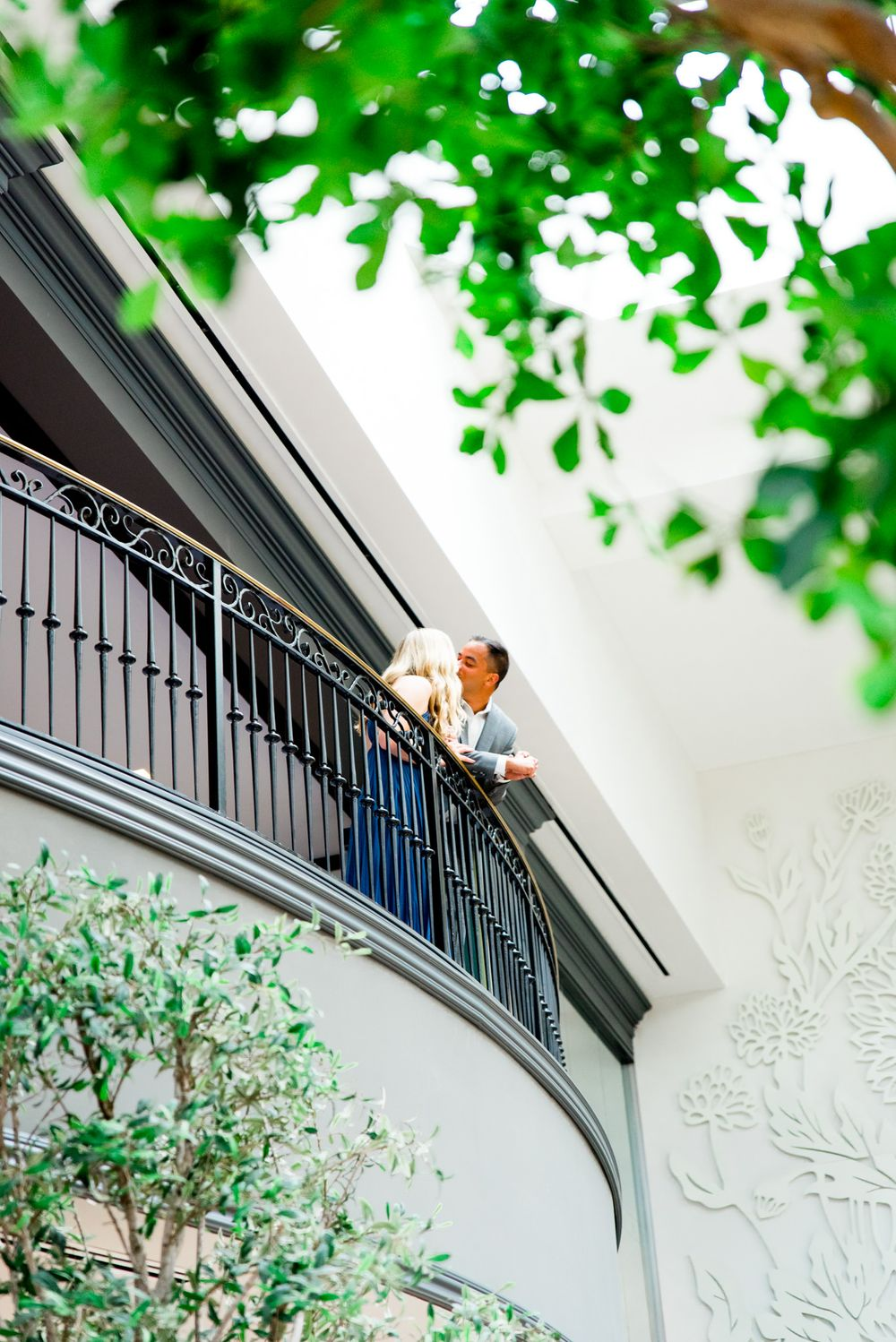young couple kisses at Juliet balcony at Lytle Park Hotel atrium