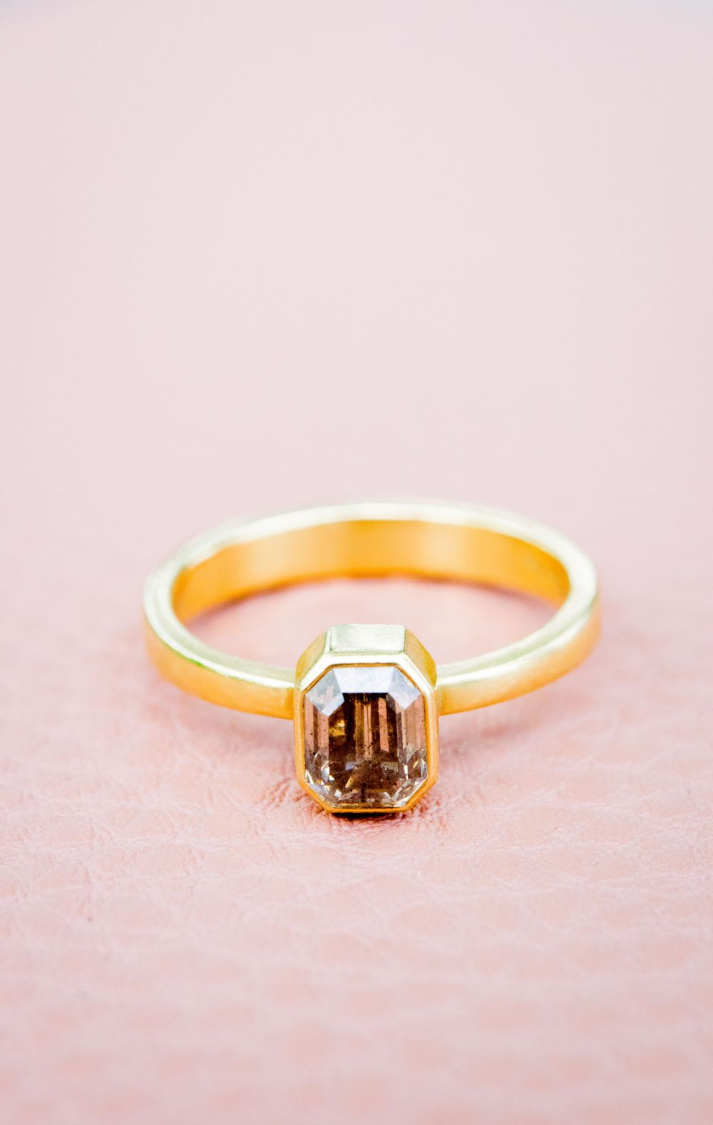gold emerald cut engagement ring with a smoky natural diamond on a pink leather bag