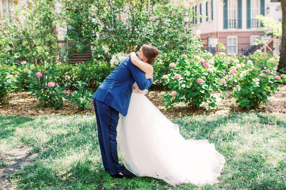 bride and groom hug during their monterey square first look in downtown savannah, ga