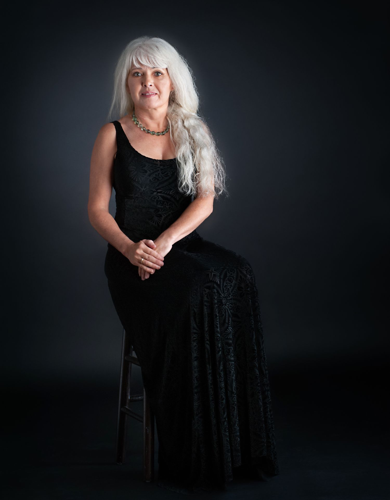 silver haired beauty sits for portrait
