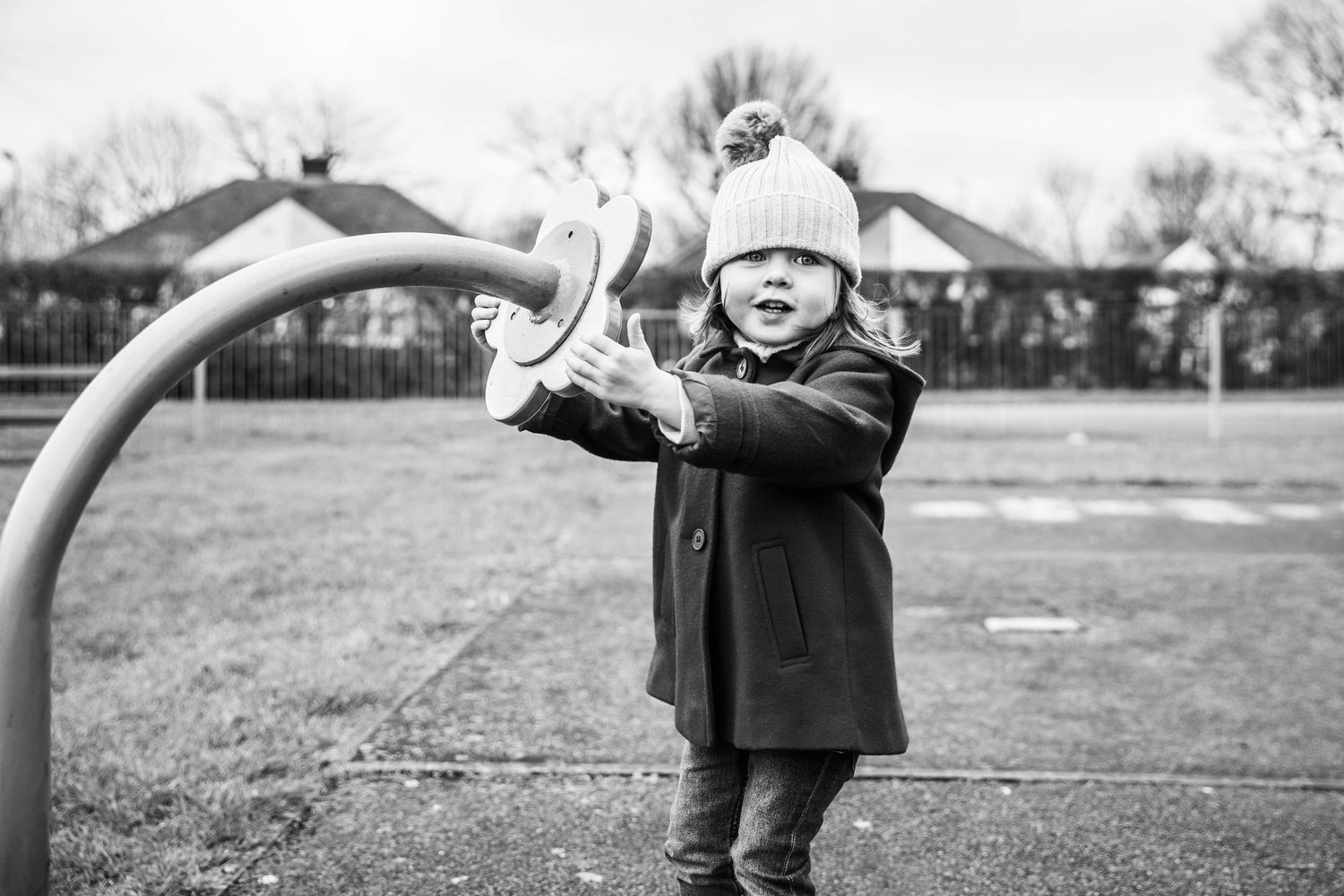 black and white portrait of girl playing in playground