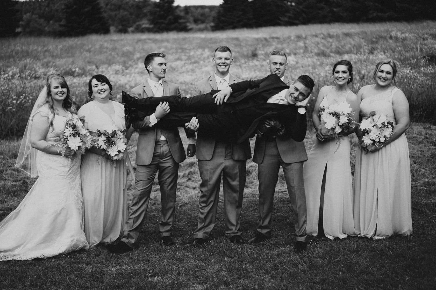 Black and white image of a wedding party holding up the groom