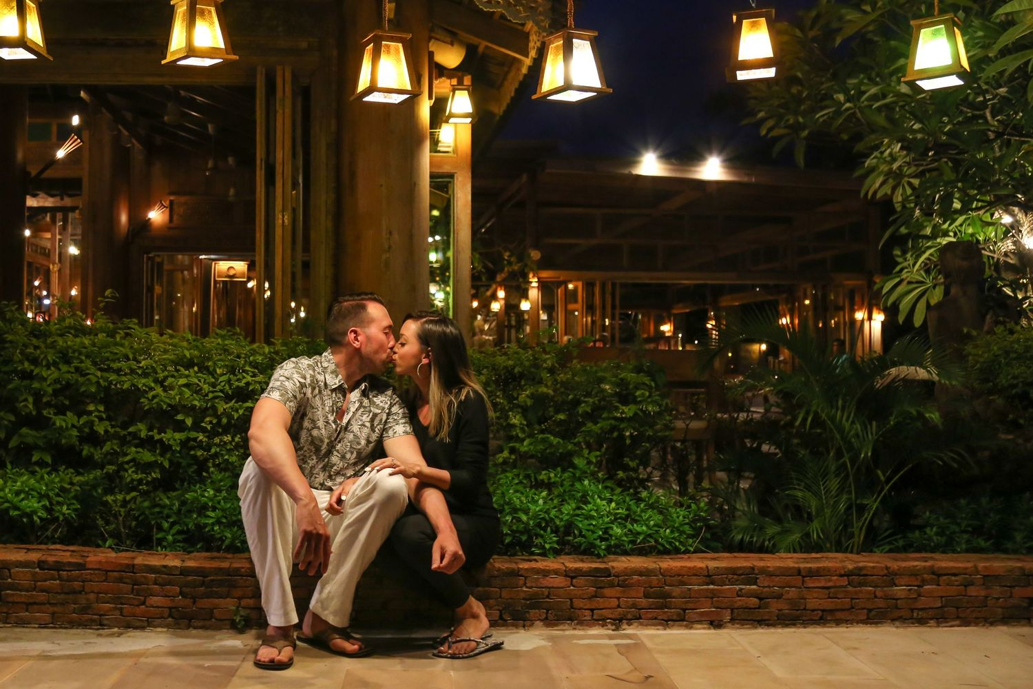 Husband and wife sitting near plants kissing in Thailand