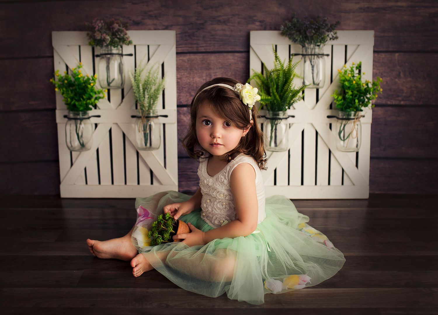 toddler in a tulle dress surrounded by plants photography studio