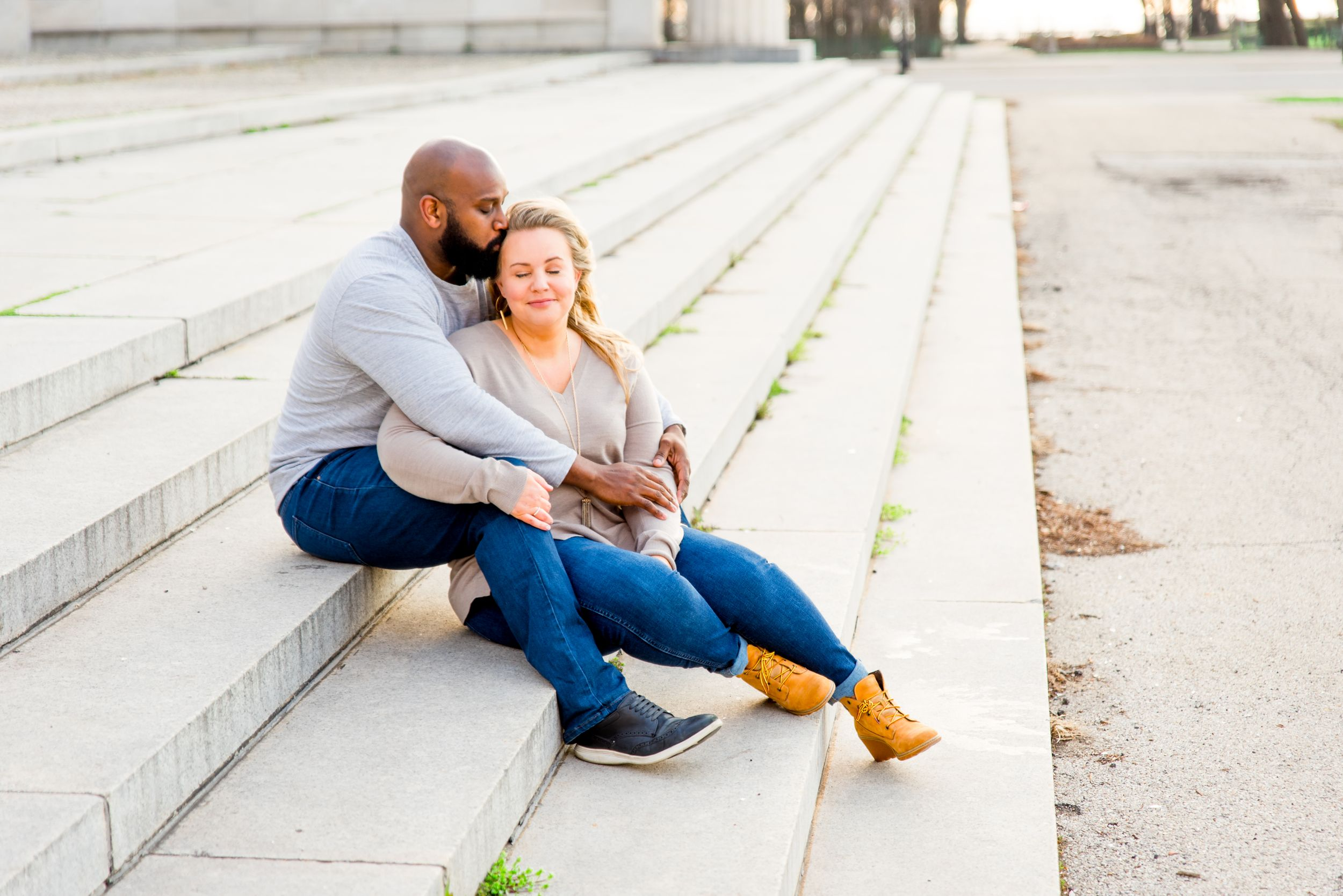 young couple sitting on steps in Grant Park for sunrise engagement pictures in CHicago