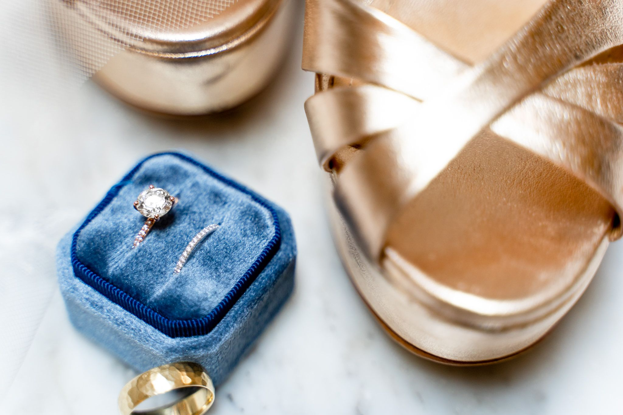 round diamond engagement ring with wedding bands in blue velvet ring box on lace wedding dress and gold wedding shoes
