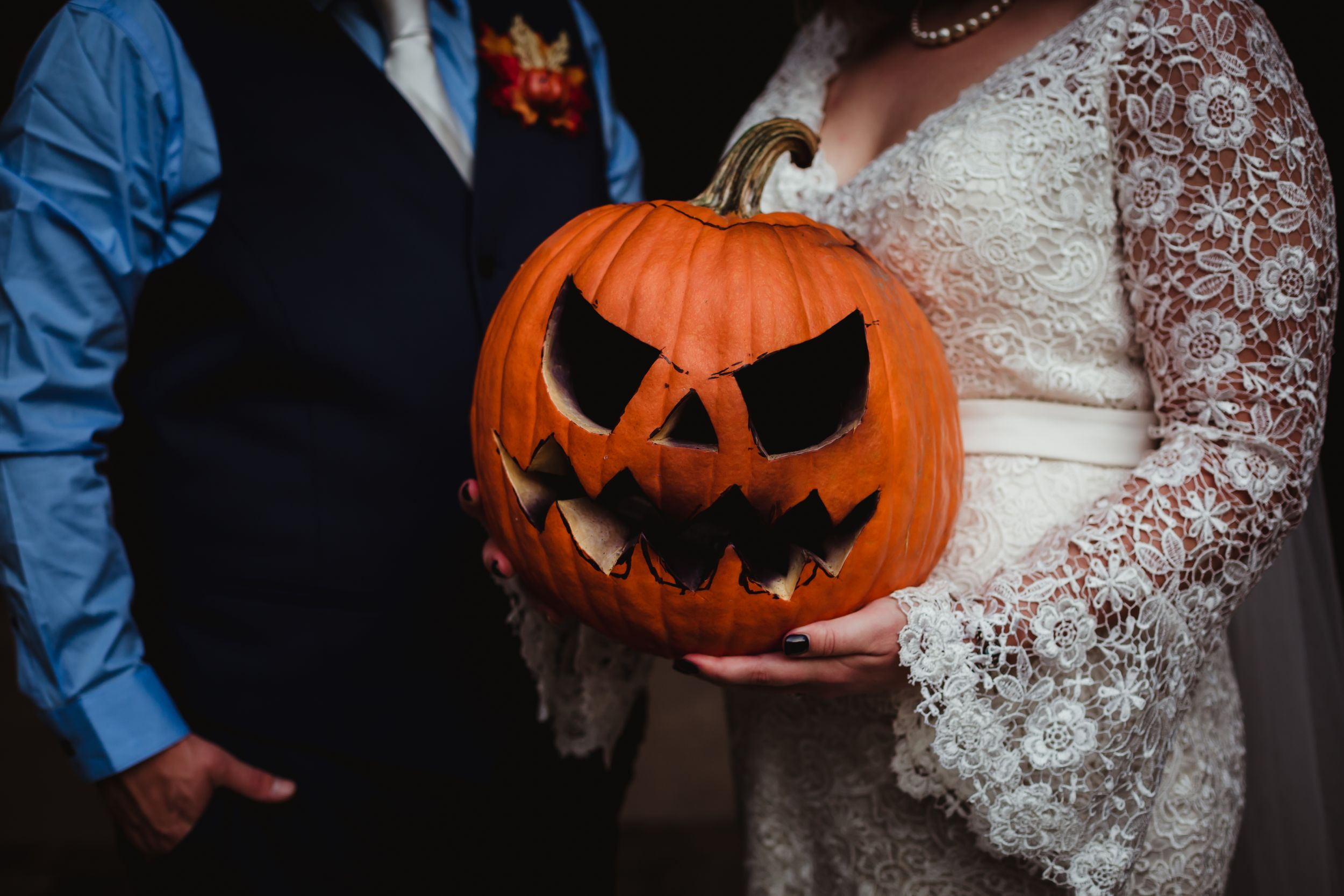 Close up of a jack-o-lantern being held by a man and woman in wedding attire.