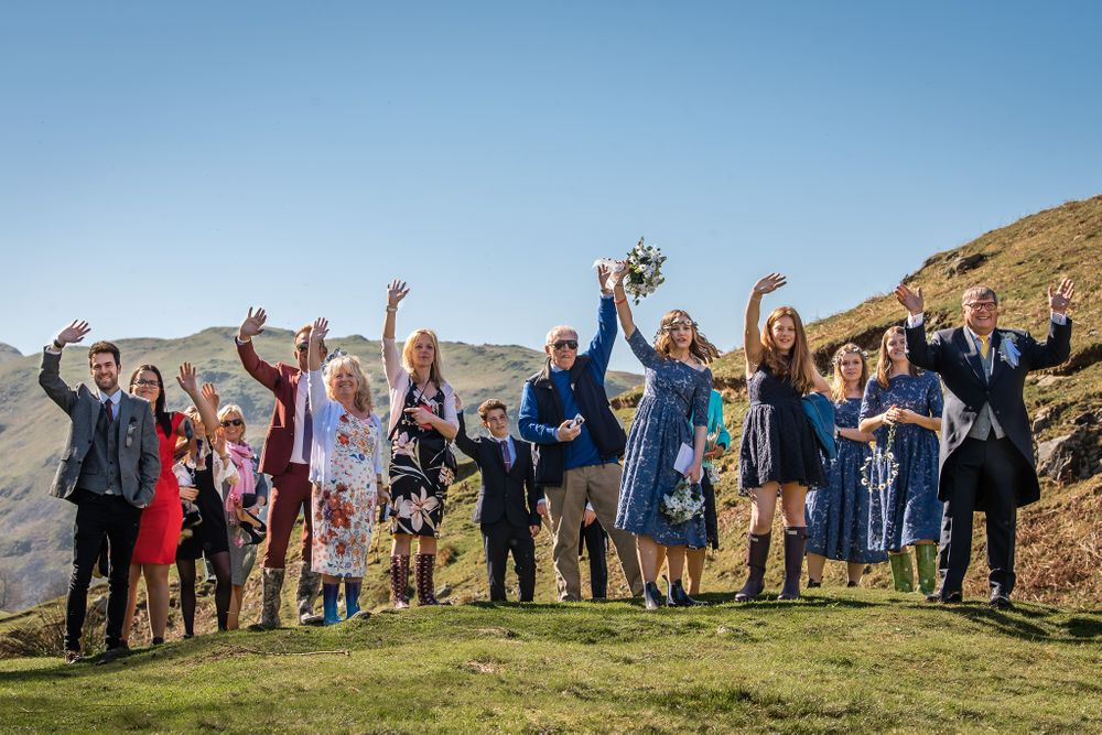 Guests waving to couple at Lake District adventure wedding