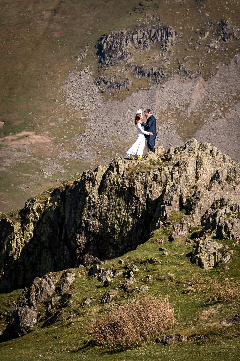 Bride and groom amongst fells at Lake District adventure wedding
