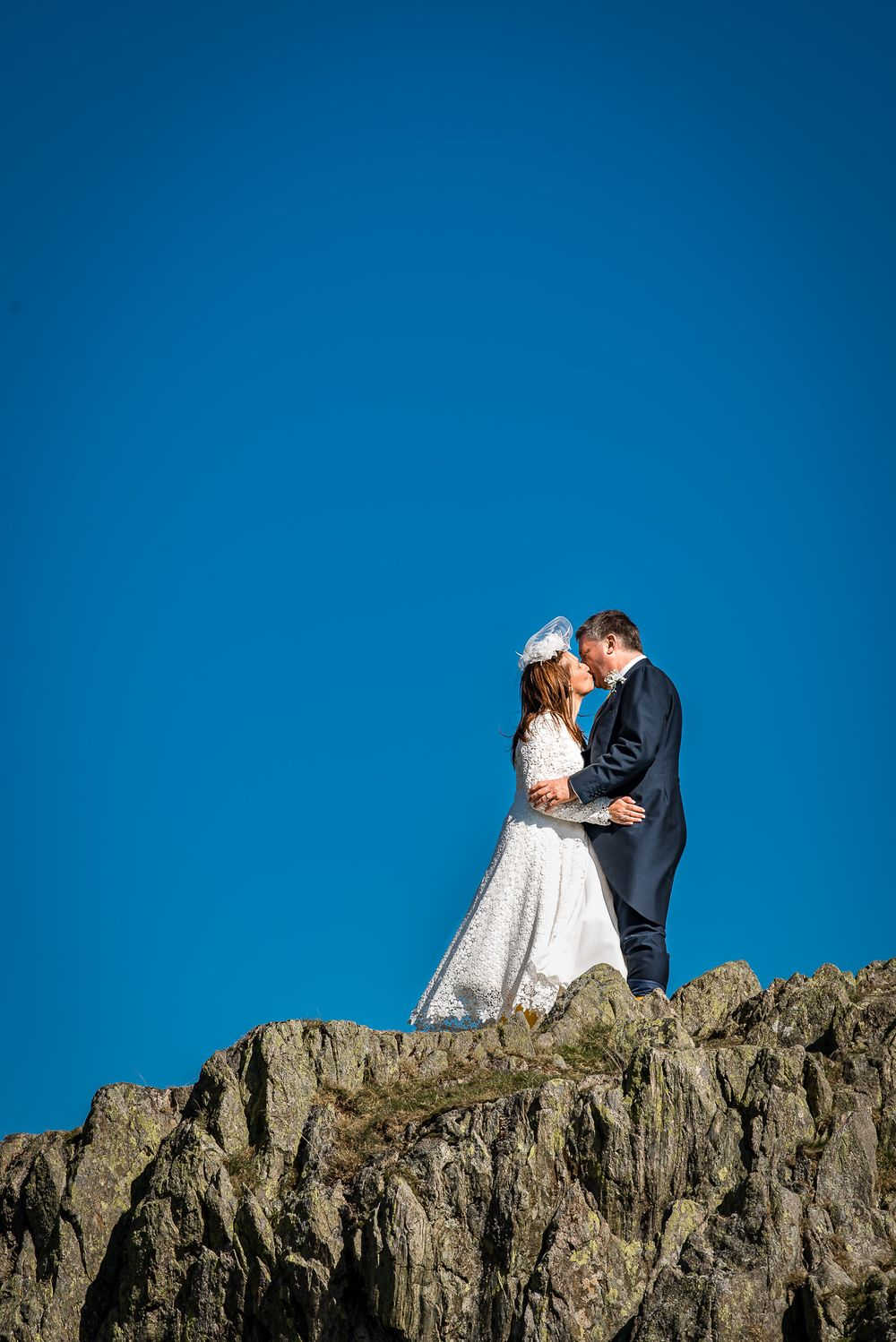 Crag top portrait of bride and groom during Lake District adventure wedding