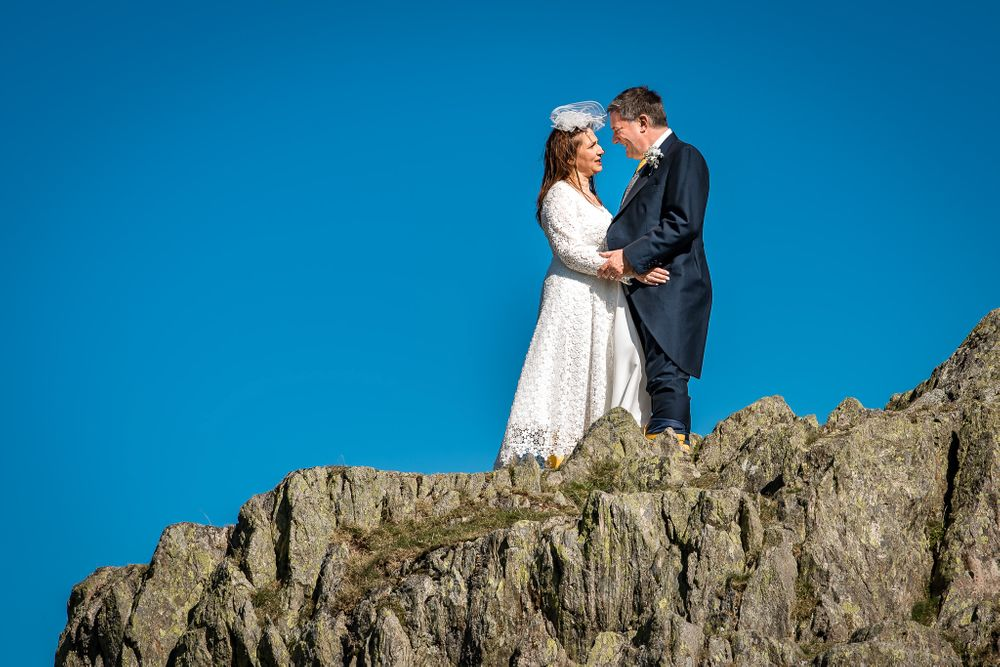 Bride and groom on top of crag at Lake District wedding