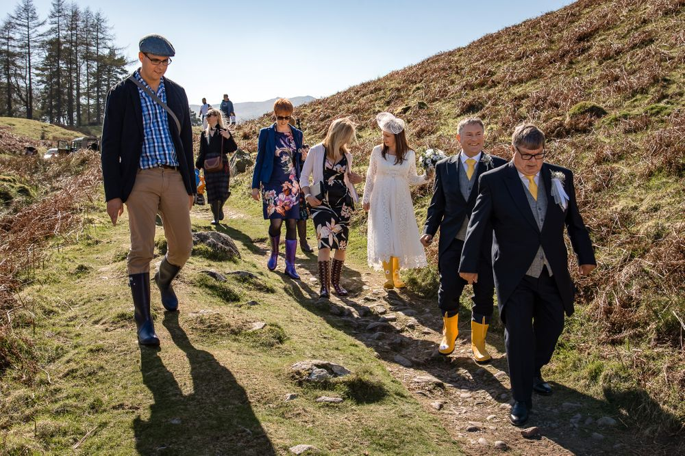 Guest join bride and groom on fell walk at Lake District wedding