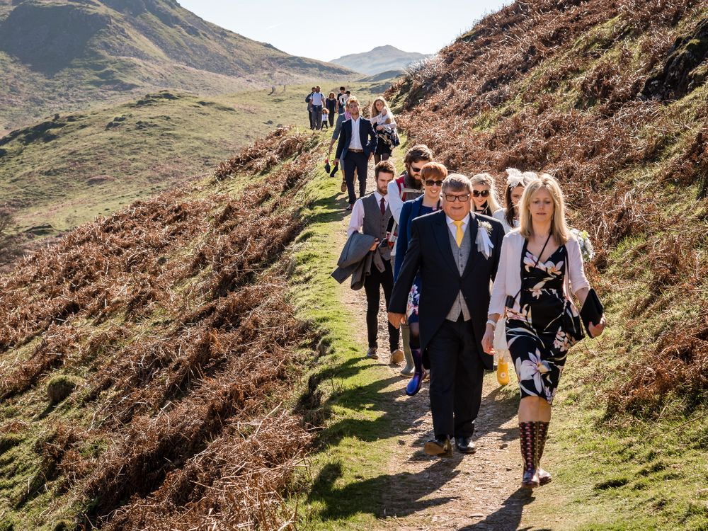 Guests walking down fellside at Lake District adventure wedding