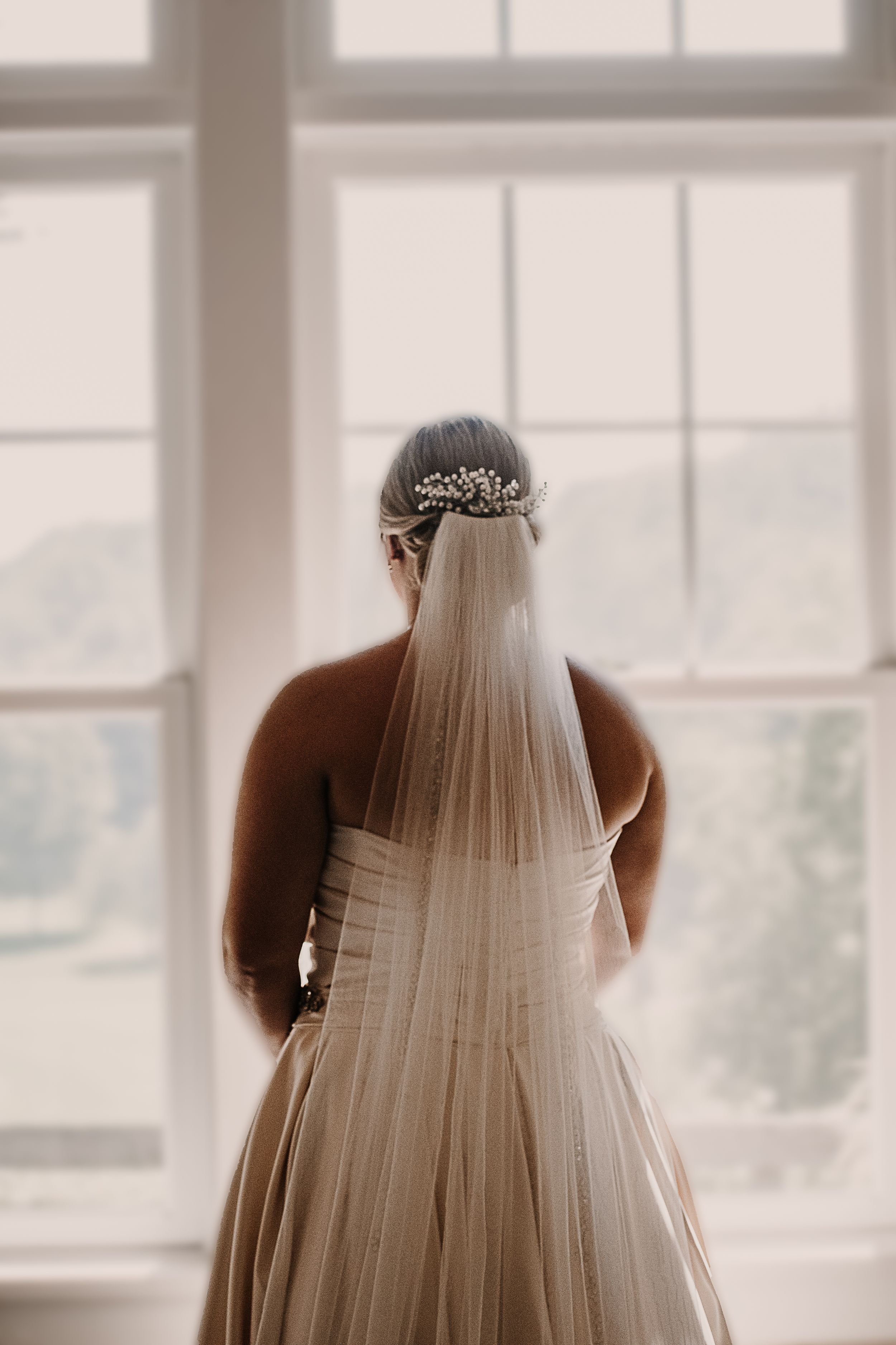 An eager and beautiful bride looks out the window from her Rochester, NY hotel