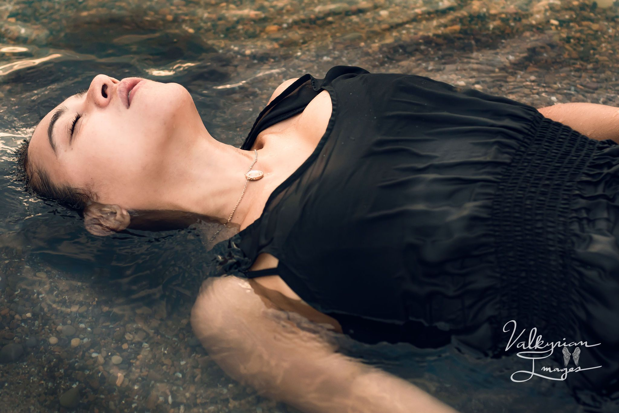 Model Rodriguez Anjonic laying down in the water at Woodlawn Beach getting her dress wet
