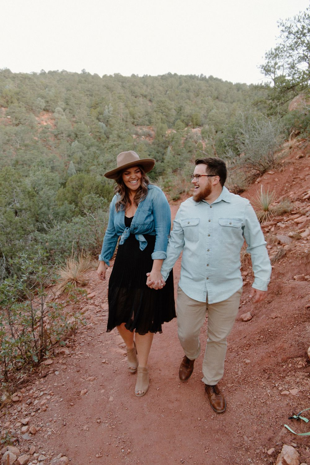 couple bumping hips on a trail in garden of the gods after getting engaged