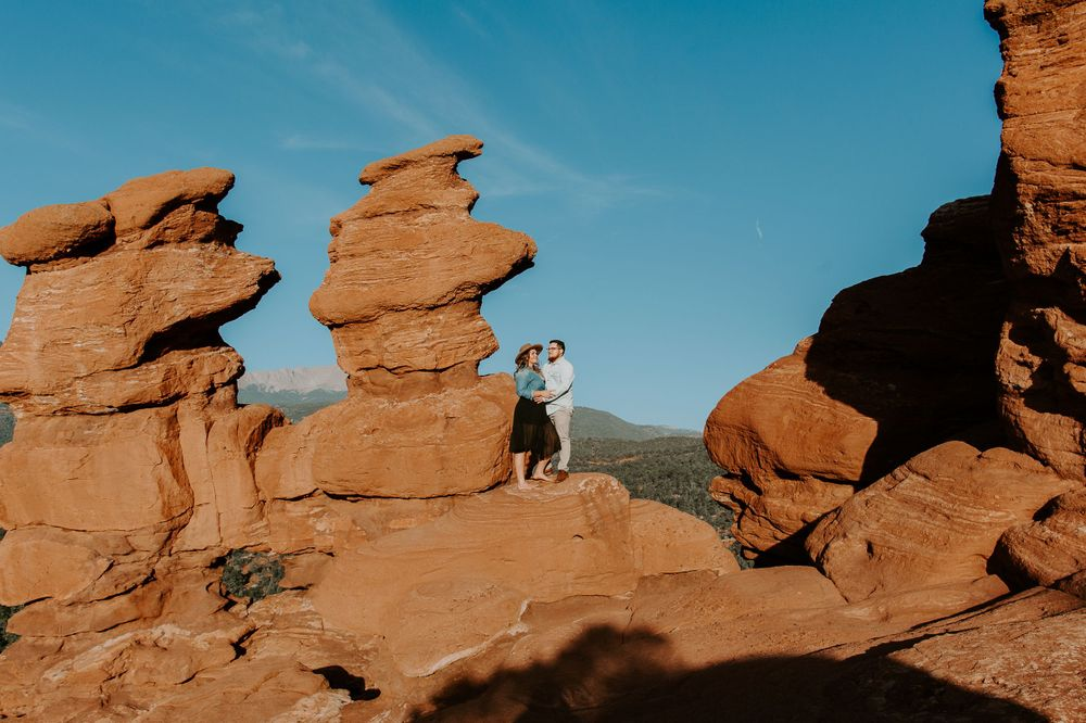 couple standing on rocks as the sunrises in Colorado springs