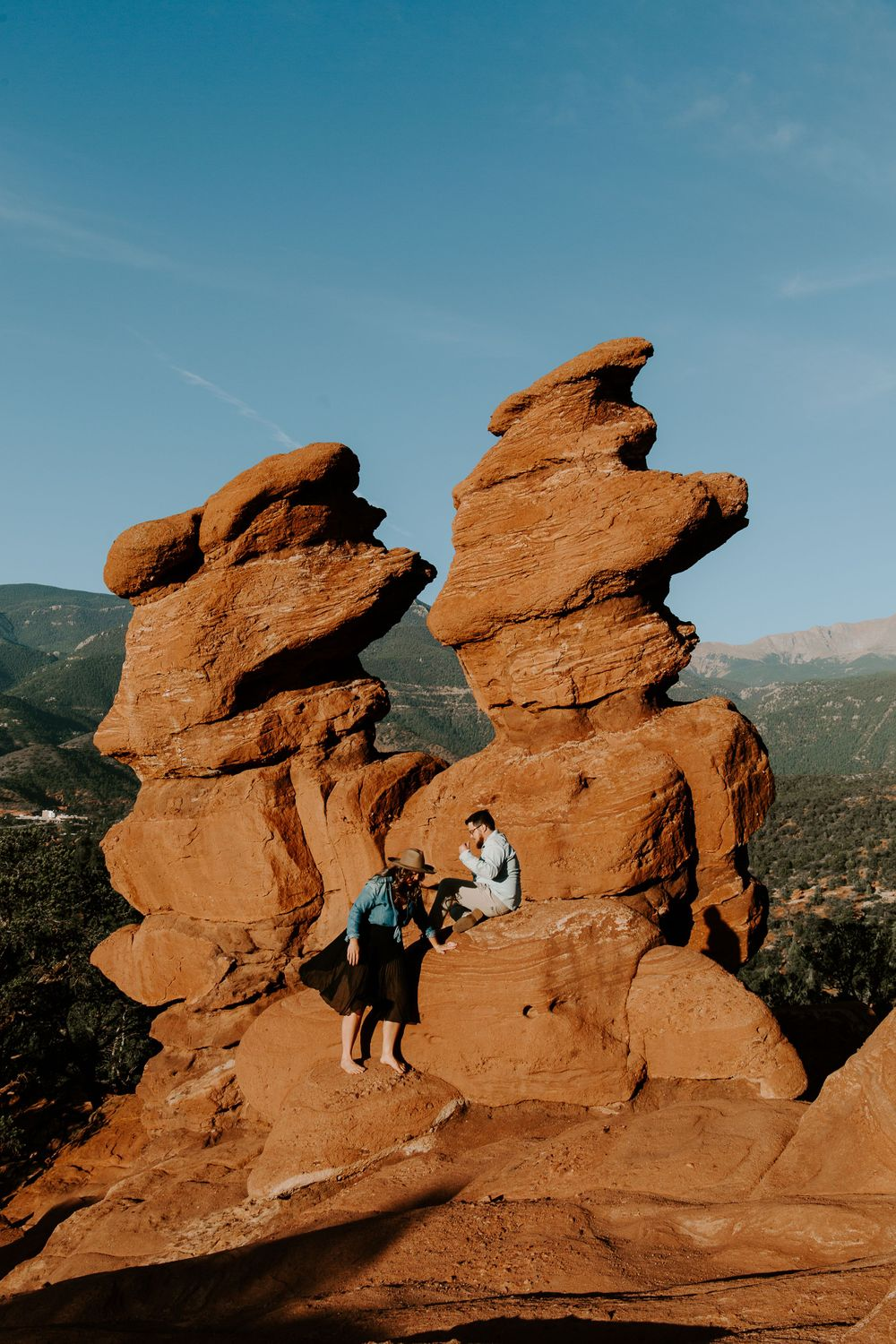 couple climbing on rocks in Colorado during their engagement