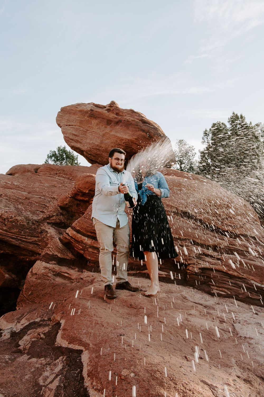 couple popping sparkling water during their adventurous couples session in Colorado Springs