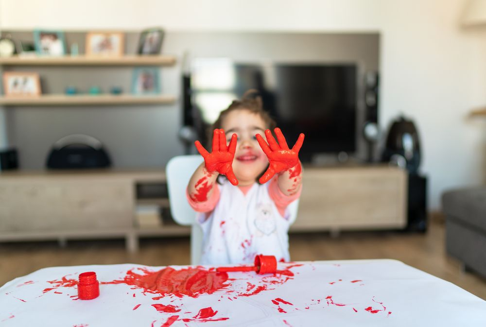 Kid with red paint on his hands - retail furniture protection plans
