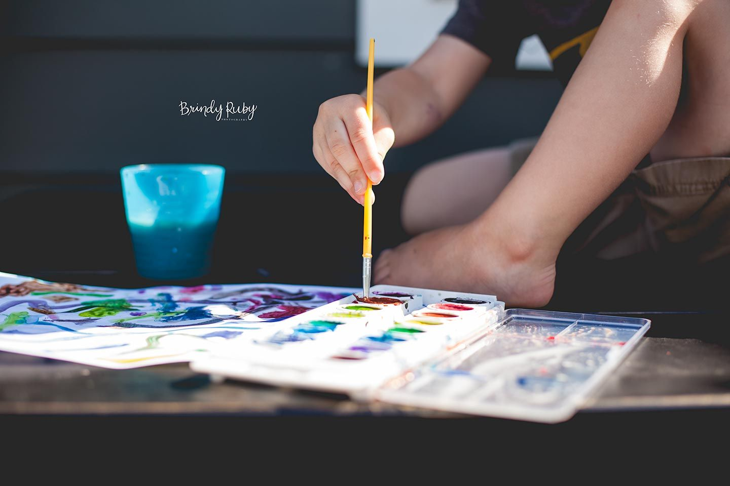 young boy dipping paint brush in watercolor palette