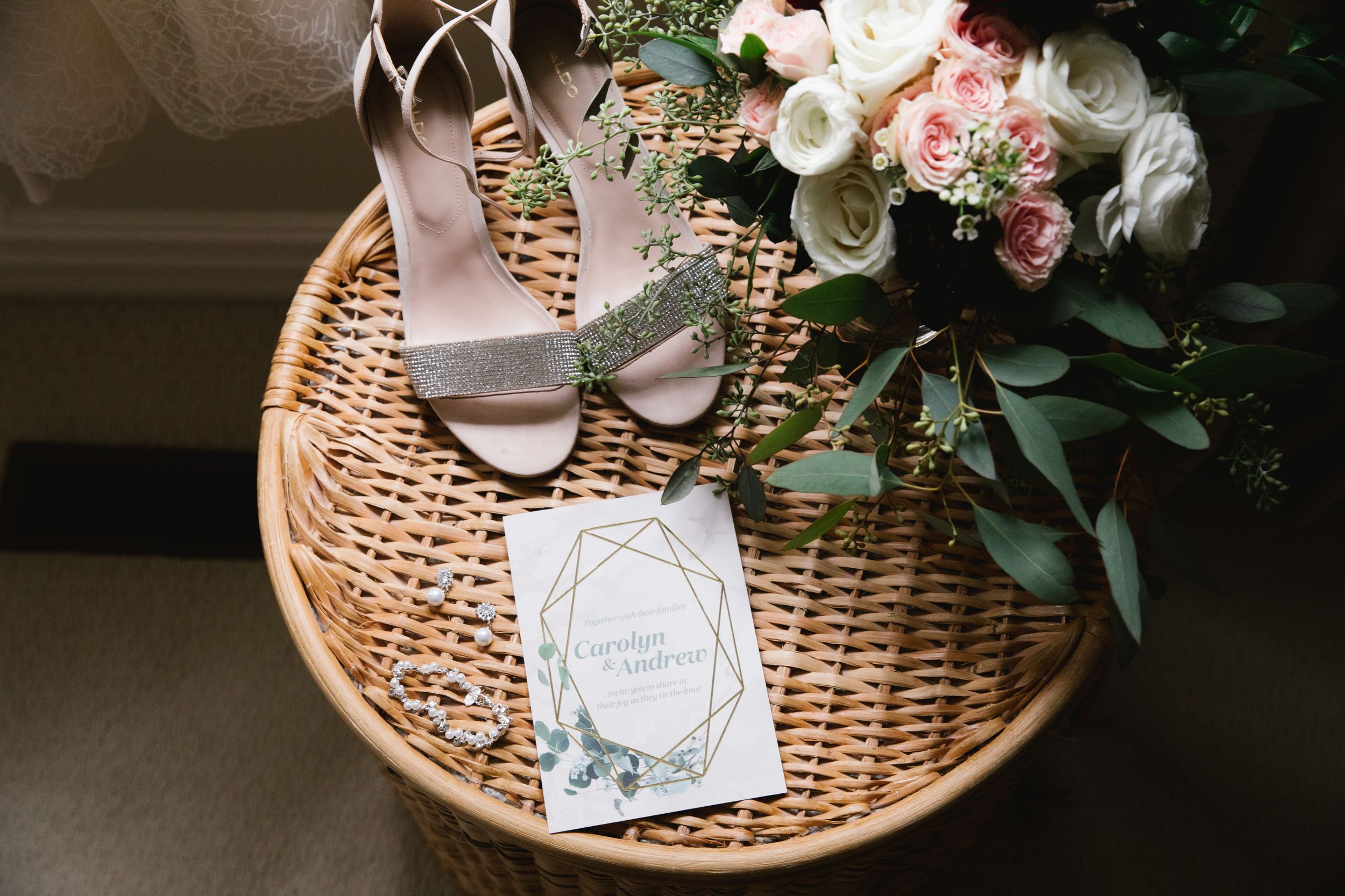 wedding details, bridal shoes, invitation, jewelry and bouquet on a wicker hamper