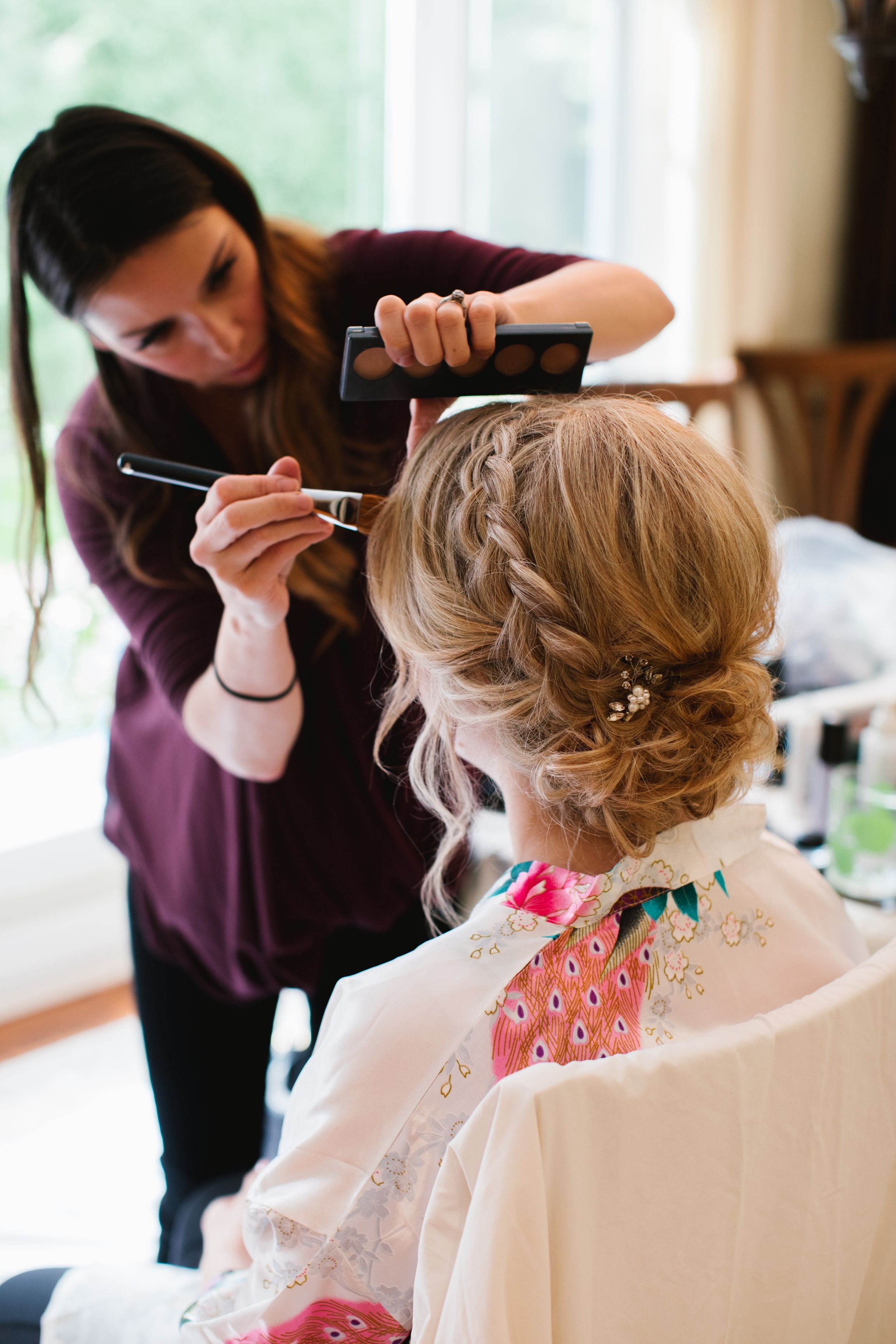 bride having her makeup done, back of her hair and makeup artist