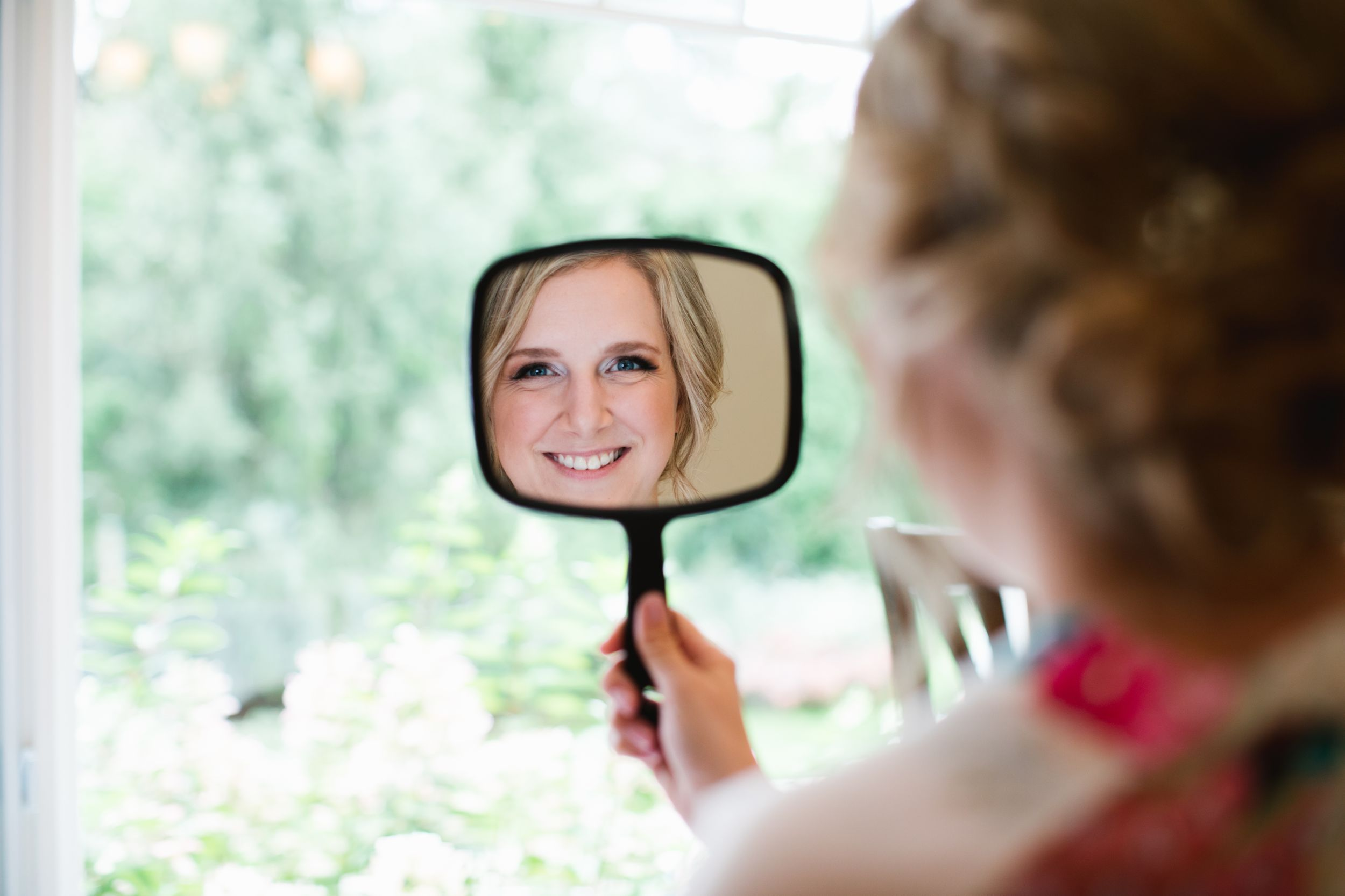 bride looking into hand mirror and smiling
