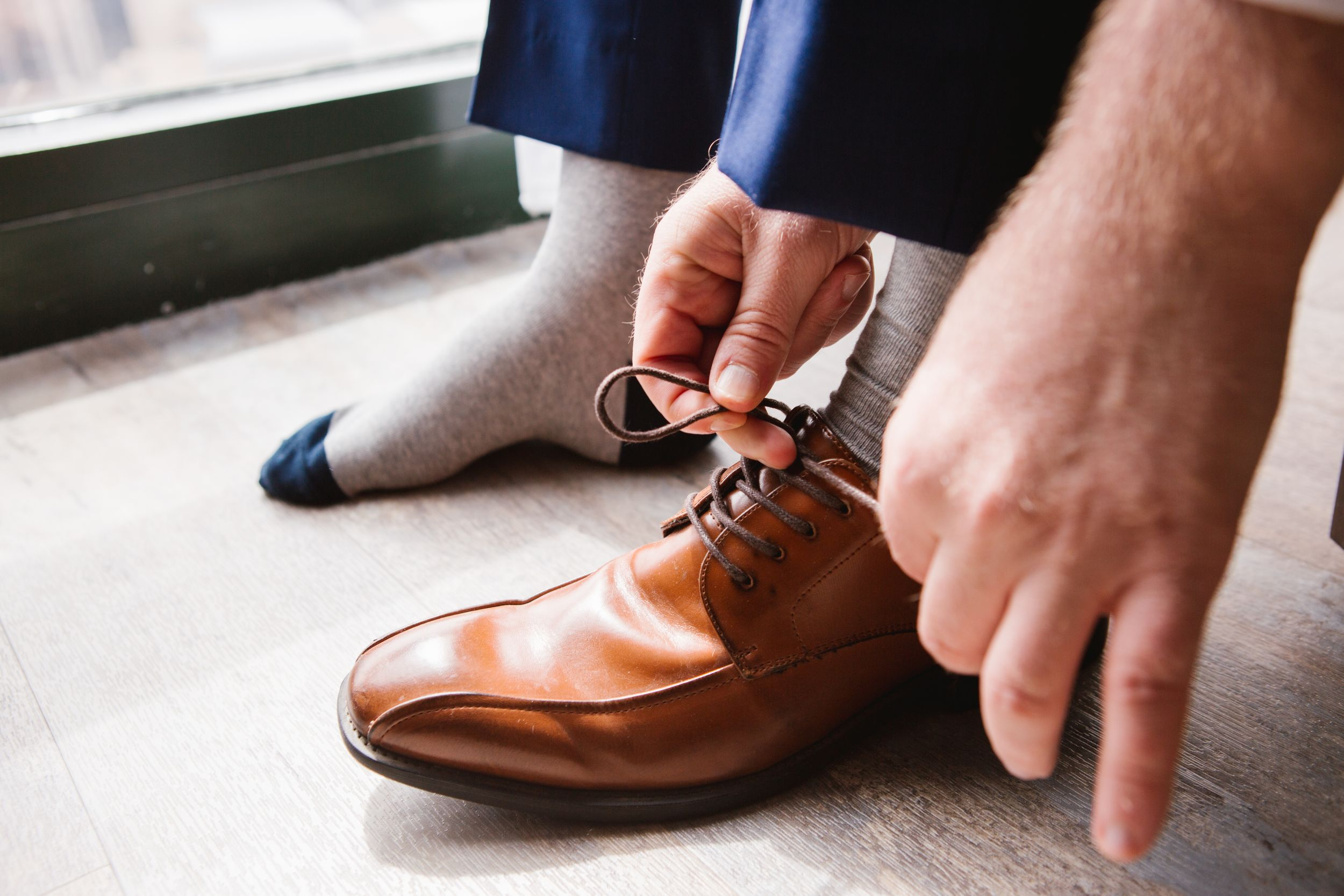 close up of groom tying shoelace on his brown wedding shoes