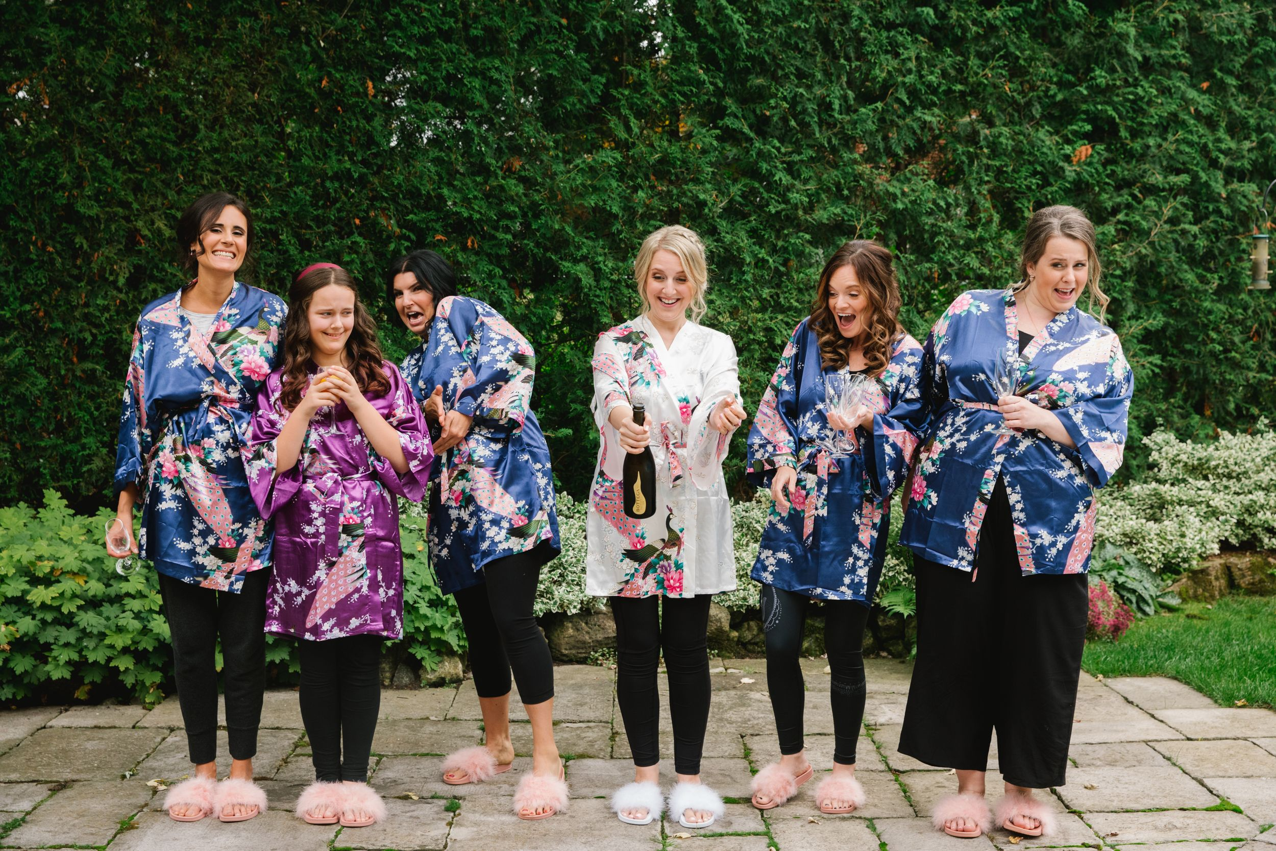 bride and bridesmaids in colourful robes popping champagne in backyard
